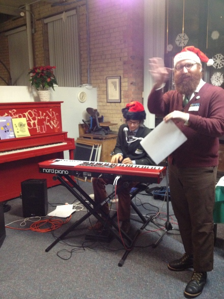 Dylan Hicks (at the piano) and Andy Sturdevant lead carolers in song